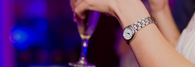 Eine Frau mit einem Glas von Prosecco in einem Club