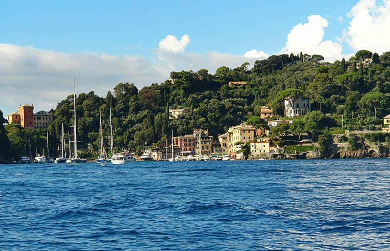 De heldere blauwe zee en huizen in Portofino