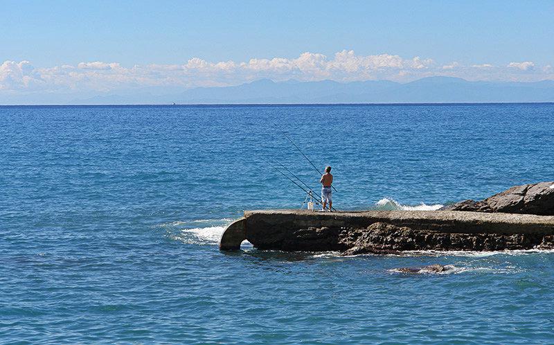 Een man is de visserij van stenen naast de zee in Recco