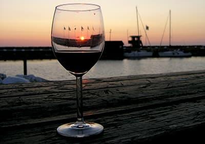 Vin rouge à côté d'un port dans la soirée en Ligurie