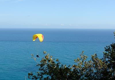Un homme est parapente sur la mer en Ligurie