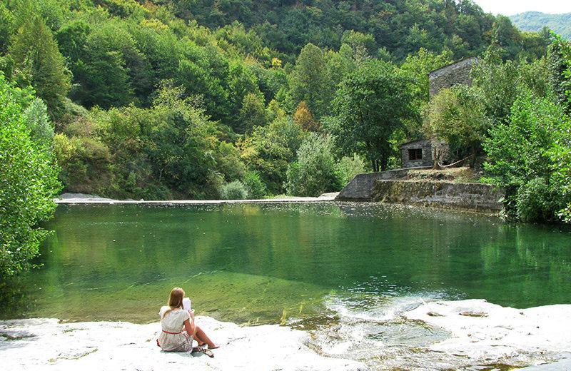 Une fille lisant un livre au bord du lac de Molini di Triora
