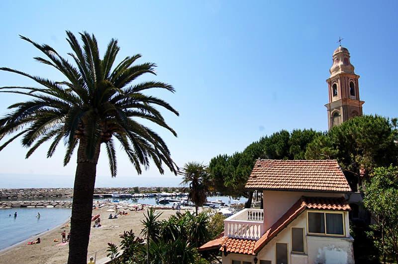 Une belle vue sur une église, un palmier et la plage de sable de San Lorenzo al Mare