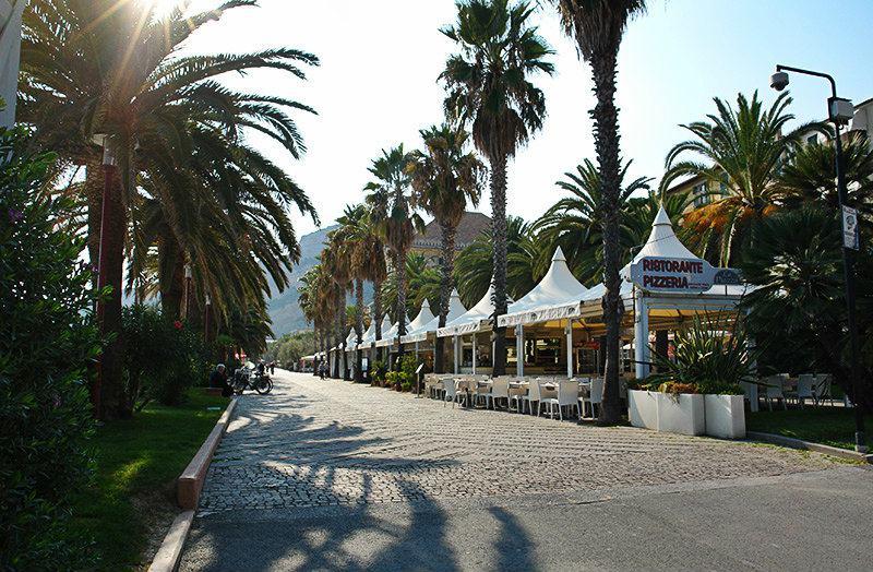 Une rue avec des palmiers à Finale Ligure